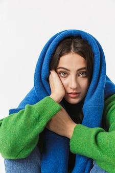 白の上に座っている特大のセーターを着ているカジュアルな若い女性の肖像画