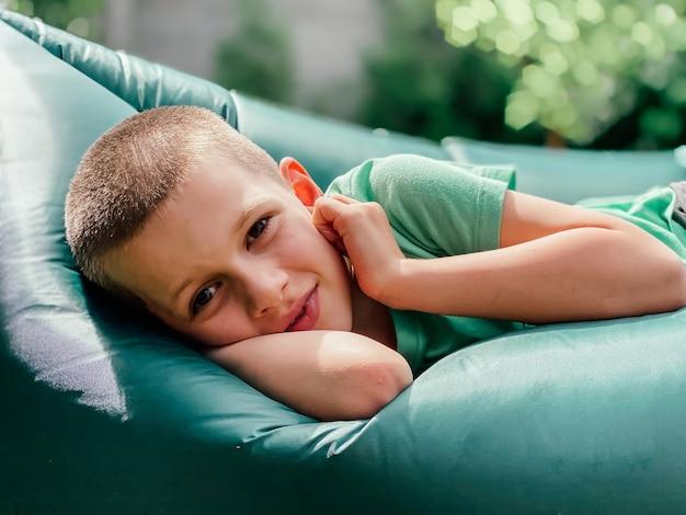 7세 백인 소년의 초상화는 녹색 티셔츠를 입은 람자크, 풍선 라운저에 앉아 있습니다. 편안한 야외 및 해변 레크리에이션, 여름 및 휴가 개념.