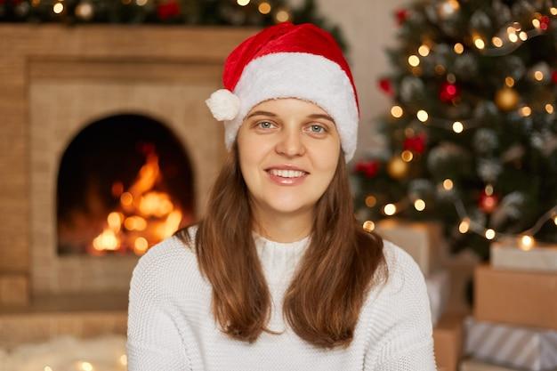 백인 여성 모델의 초상화는 벽난로와 x-mas 트리, 이빨 미소를 가진 아가씨 집에서 포즈를 취하는 산타 모자와 흰색 스웨터를 착용합니다.