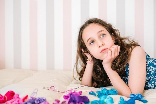 Портрет кавказской девушки, лежащей в постели и думающей о том, чтобы сделать браслеты из цветных ниток