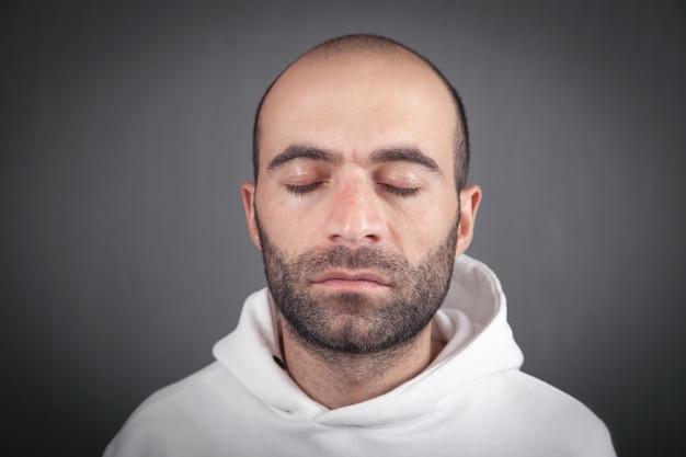 目を閉じた白人男性の肖像画。