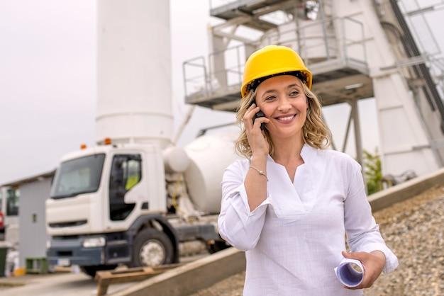 Портрет кавказской женщины в желтой каске на телефоне и улыбающейся на стройке