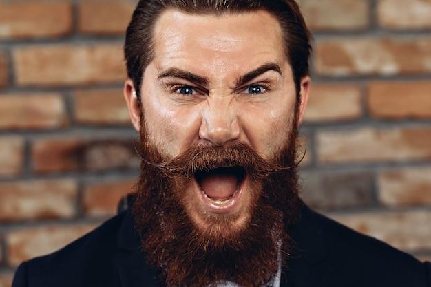 スーツ、ハッサーの口ひげとあごひげを身に着けて、レンガの壁に向かってポーズをとっているカリスマ的なハンサムな男の肖像画。コンセプトos式