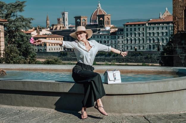 フィレンツェの噴水の近くに座っている魅力的な女の子の肖像画。サンタマリアデルフィオーレの眺め。イタリア。