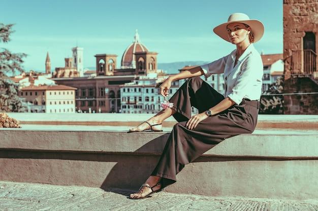 피렌체의 분수 근처에 앉아 있는 매력적인 소녀의 초상화. 산타 마리아 델 피오레의 전경. 관광 개념입니다. 이탈리아. 혼합 매체