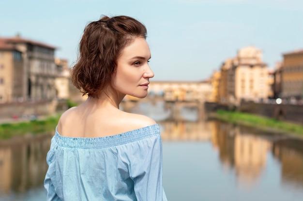 フィレンツェの橋の上に立っている魅力的な女の子の肖像画。アルノ川。ヴェッキオ橋の眺め。イタリア。
