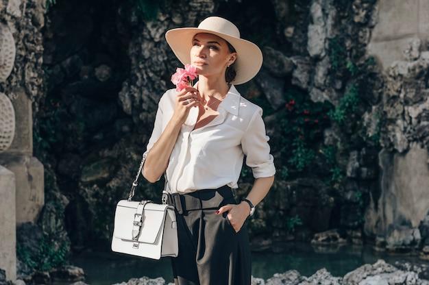 피렌체의 미켈란젤로 광장에 서있는 매력적인 여자의 초상화. 그녀는 꽃 냄새를 맡고 기대합니다.