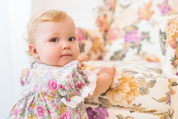 花柄の椅子の近くに立っている美しいドレスを着た魅力的な少女の肖像画。