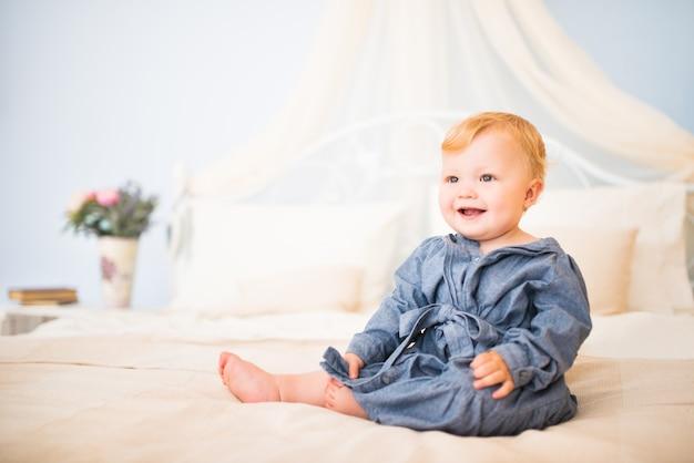 大きなシックなベッドに座っている青いドレスを着た魅力的な少女の肖像画。ナイーブな小さな子供たちのコンセプト。