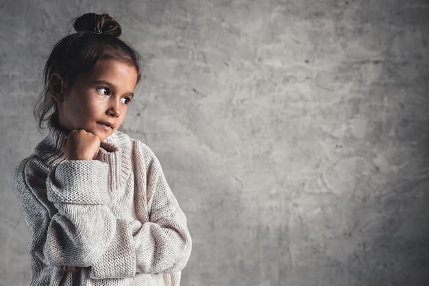 灰色の背景にベージュのセーターの魅力的な少女の肖像画