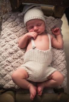 居心地の良いベッドで寝ているニット帽とショートパンツで魅力的な新生児の小さな幼児の肖像画。かわいらしいキッズコンセプトのキュート。子供の頃と素朴な概念