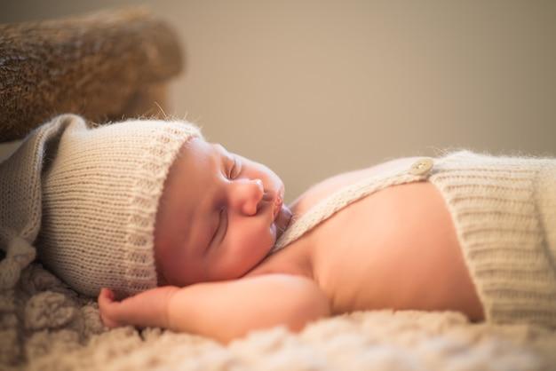 居心地の良いベッドで寝ているニット帽とショートパンツで魅力的な新生児の小さな幼児の肖像画