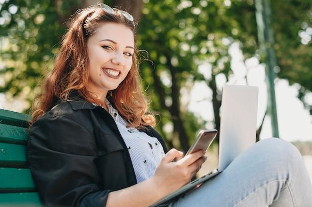 彼女の足にラップトップとカメラの笑顔を見ている片手にスマートフォンを持ってベンチに座っている魅力的なプラスサイズの女性の肖像画。