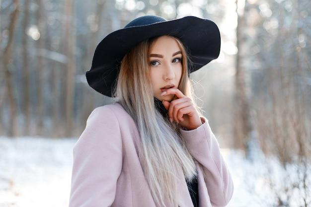 세련된 따뜻한 핑크 코트에 검은 우아한 모자에 매력적인 예쁜 젊은 여자의 초상화