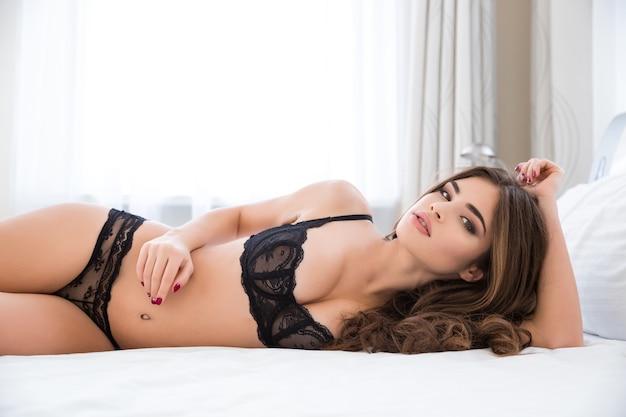 Портрет очаровательной сексуальной женщины в нижнем белье, лежащей на кровати и смотрящей в камеру