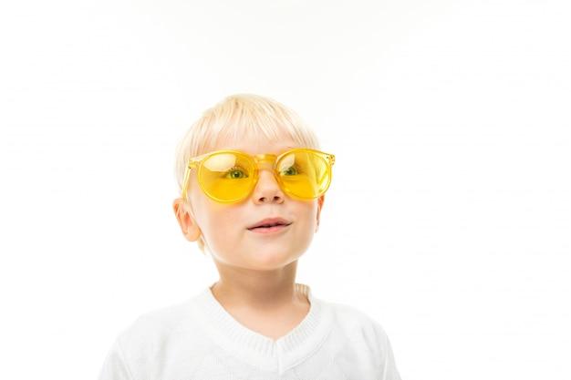 Портрет очаровательного улыбающегося белокурого мальчика в очках, одетого в белую футболку на белом