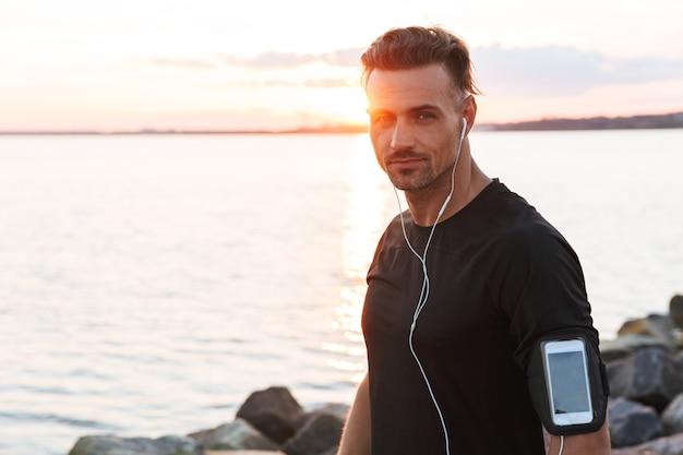 Портрет очаровательного спортсмена, слушающего музыку