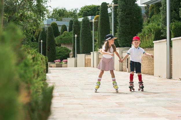 公園でローラースケートで一緒にスケートをする魅力的な10代のカップルの肖像画。 10代の白人の男の子と女の子。