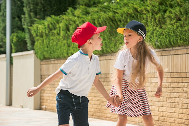 Портрет очаровательной подростковой пары кататься на коньках вместе на роликовых коньках в парке.