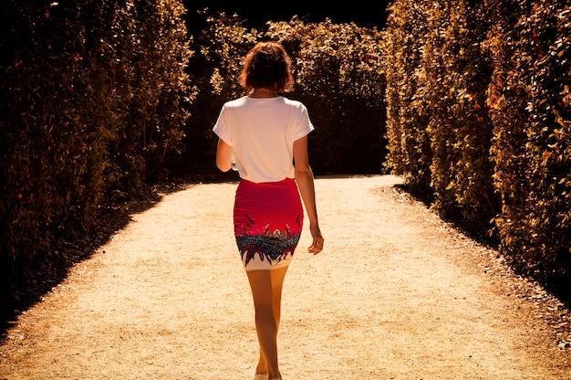 Портрет очаровательной женщины в садах боболи. вид сзади. концепция туризма и путешествий. смешанная техника
