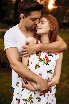 데이트하는 동안 키스하기 전에 닫힌 눈으로 일몰에 대해 관능적 인 포용 매력적인 젊은 부부의 초상화.