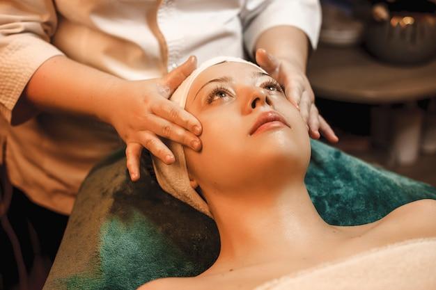 Портрет очаровательной молодой женщины, отдыхающей во время массажа лица в оздоровительном спа-центре.