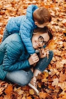 カメラを笑いながら屋外で子供と遊んでいる魅力的な若い母親の肖像画。