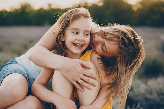 그녀는 꽃의 분야에서 일몰에 웃고있는 동안 그녀의 작은 딸을 껴안고 뺨에 그녀를 키스 매력적인 젊은 여자의 초상화.
