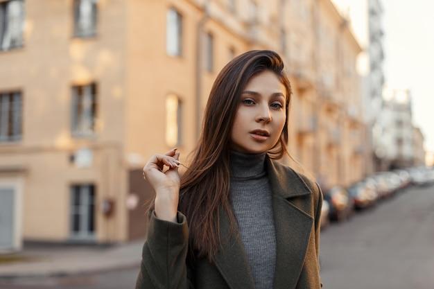 빈티지 건물의 벽에 세련된 회색 코트에 매력적인 젊은 여자의 초상화. 세련된 소녀.