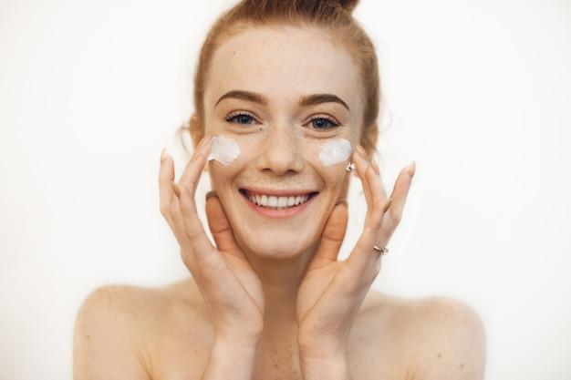 彼女の頬に両手クリームで遊んでいる間笑っているカメラを見ている魅力的な若い女性の肖像画。