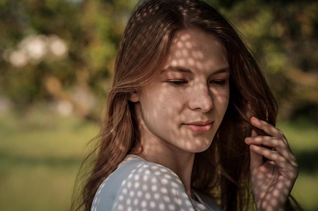 屋外の魅力的な若い女性の肖像画。光と影。珍しい影で覆われた少女の顔の興味深い肖像画