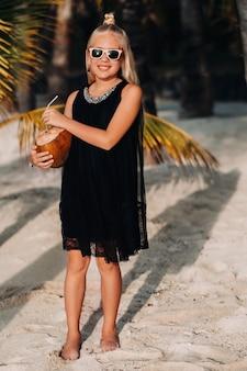 이국적인 해변의 야자수 배경에 코코넛 칵테일을 든 쾌활한 9세 소녀의 초상화. 모리셔스 섬 해변에서 코코넛을 든 어린 소녀.