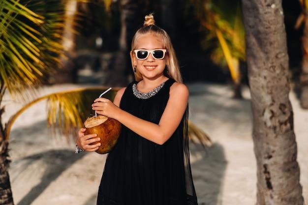 エキゾチックなビーチのヤシの木を背景にココナッツカクテルと陽気な9歳の少女の肖像画。モーリシャス島のビーチでココナッツと少女