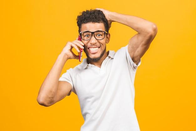 Портрет веселого афро-американского парня разговаривает по мобильному телефону