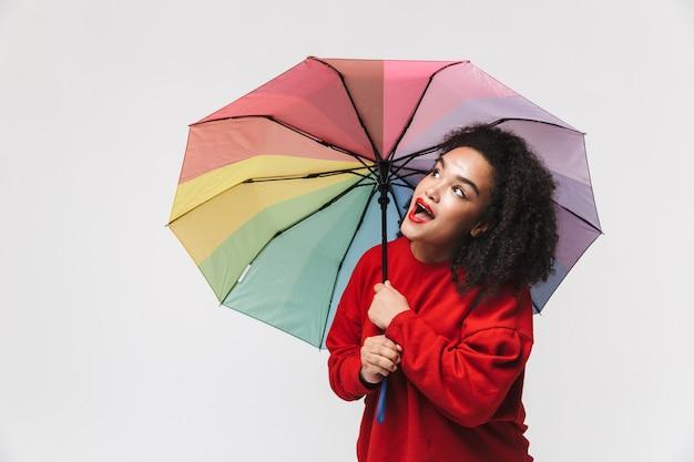 Портрет веселой африканской женщины, стоящей изолированно на белом фоне и держащей красочный зонтик