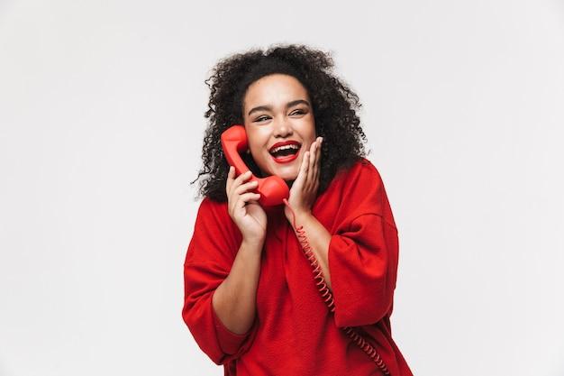 Портрет веселой африканской женщины, стоящей изолированно на белом фоне и разговаривающей по стационарному телефону