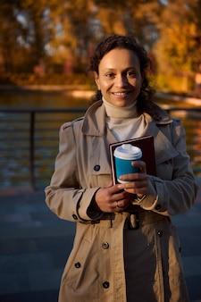 테이크아웃 커피 한 잔과 낙엽이 떨어지는 가을 공원 호수 배경에서 카메라를 보며 웃고 있는 손책을 들고 있는 쾌활한 아프리카 여성의 초상화. 가을 야외 레저. 휴양