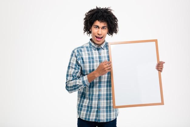 Портрет веселого афроамериканца, держащего пустую доску, изолированную на белой стене