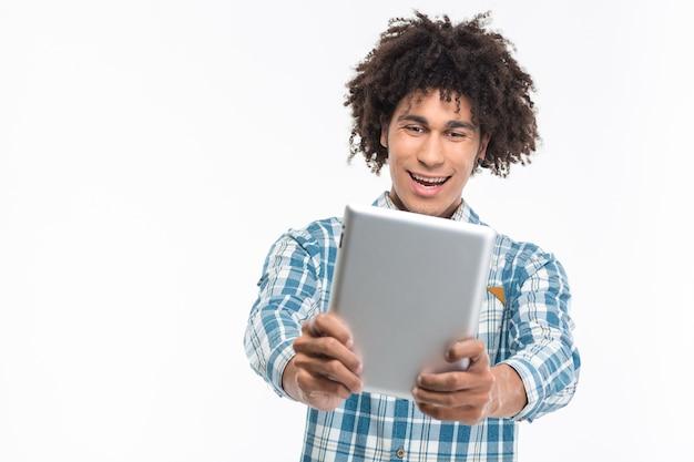 흰 벽에 고립 된 태블릿 컴퓨터를 사용하는 쾌활한 아프리카 계 미국인 남자의 초상화