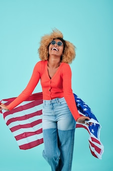Портрет веселой афро женщины, держащей флаг сша во время празднования дня независимости на изолированном фоне.