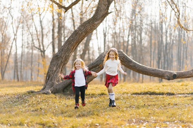 陽気で幸せな子供の肖像画、赤いチェックのシャツの女の子と公園で晴れた日に遊んでいる黒のレギンス