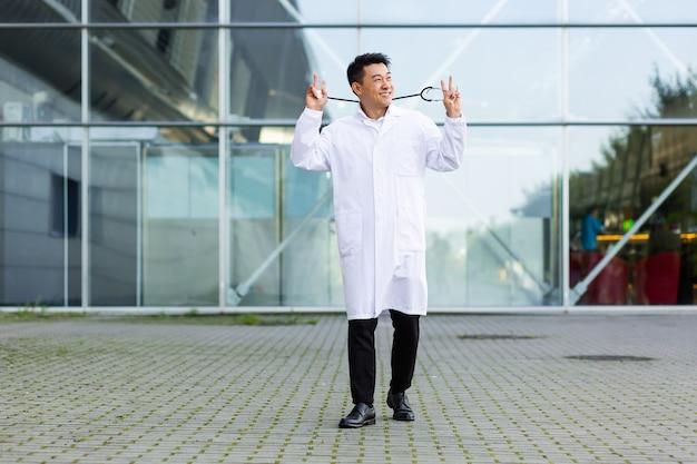 外の近代的なクリニックの背景で行われた作業の結果に満足して踊る陽気なアジアの医者の男の肖像画