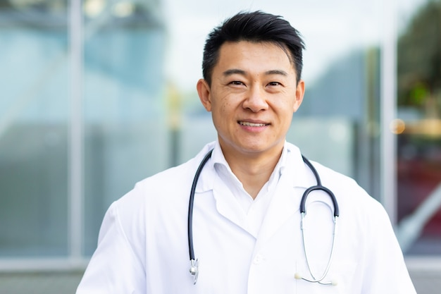 屋外のモダンなクリニックの背景に笑みを浮かべて陽気なアジアの医者の男の肖像画