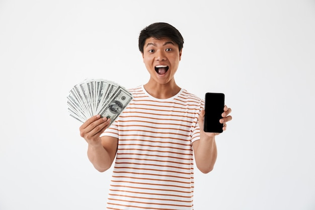Портрет веселого азиатского мужчины, держащего деньги
