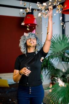 青い巻き毛と彼女の手に紙吹雪雨の下に立って祝うシャンパンで陽気な美しいアフリカの女の子の肖像画