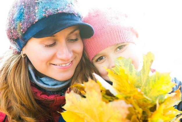 공원에서 산책하는 동안 그녀의 손에 가을 단풍 노란 잎을 들고 그녀의 예쁜 딸과 함께 쾌활 한 아름 다운 젊은 어머니의 초상화. 개념 가족 유대 및 전통