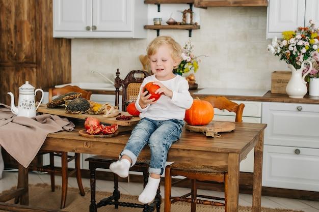 Портрет жизнерадостного мальчика сидя на красивом внутреннем кухонном столе с тыквами.