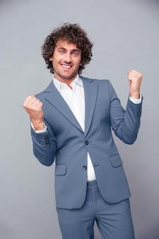 Портрет веселого бизнесмена, празднующего успех над серой стеной