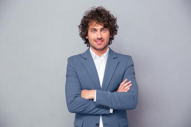 Портрет веселого бизнесмена, стоящего со скрещенными руками над серой стеной