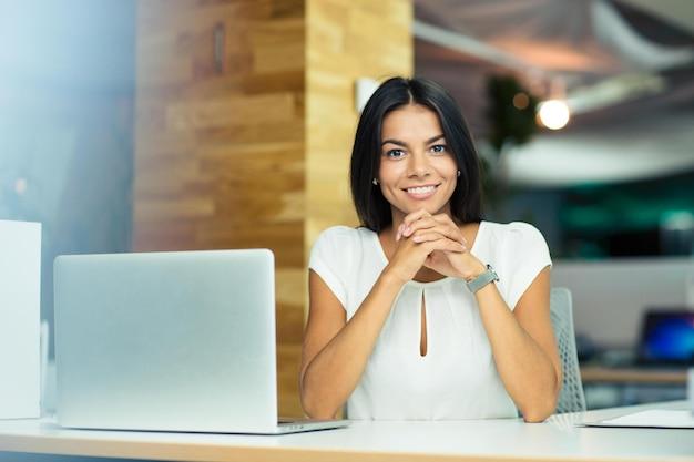 Портрет веселой деловой женщины, сидящей за столом в офисе